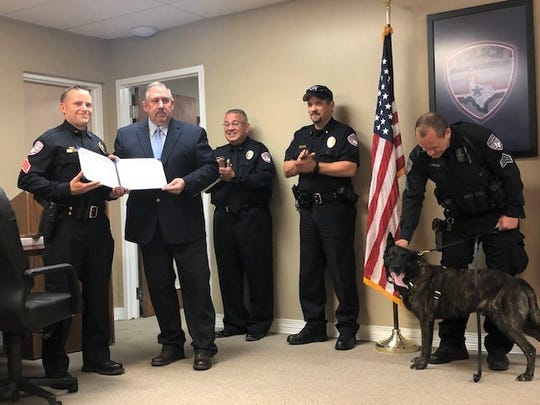 San Angelo Police Chief Frank Carter hands K-9 supervisor, Sgt. Brian Gesch,  an official certificate of retirement for K-9 Thor.