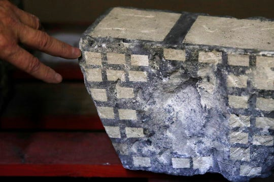 In this photo taken on Wednesday, Oct. 9, 2019, stone expert Jean-Didier Mertz shows the tests of laser cleaning technique on a broken vault stone from Notre Dame cathedral in a warehouse at Champs-sur-Marne, west of Paris. Scientists at the French government's Historical Monuments Research Laboratory are using these objects as clues in an urgent and vital task, working out how to safely restore the beloved Paris cathedral and identify what perils remain inside in a race against the clock.
