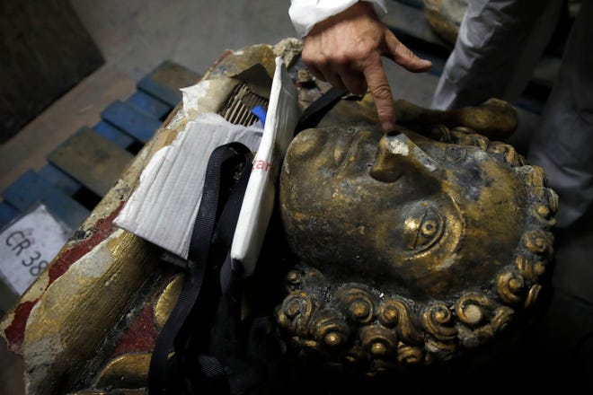 In this photo taken on Wednesday, Oct. 9, 2019, stone expert Jean-Didier Mertz, shows a broken nose of the golden angel that was once atop Notre Dame cathedral, in a warehouse at Champs-sur-Marne, west of Paris. Scientists at the French government's Historical Monuments Research Laboratory are using these objects as clues in an urgent and vital task, working out how to safely restore the beloved Paris cathedral and identify what perils remain inside in a race against the clock.