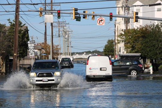 Motorists navigate flooded roads in downtown Ocean City Friday, Oct. 11.