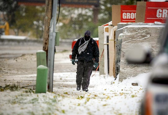 A pedestrian walks along West Main Street at the gap during the first snowfall of the winter season on Thursday in Rapid City. A powerful winterlike storm moving through the Great Plains was closing schools and causing travel headaches in several states, authorities said Thursday.