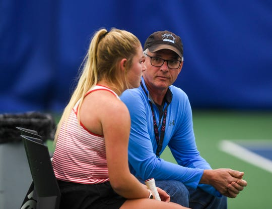 Lincoln coach Tom Krueger talks to Ava Leonard between sets in an intense match against St. Thomas More's Bridget Raymond during the state championship tournament on Friday, Oct. 11, 2019.