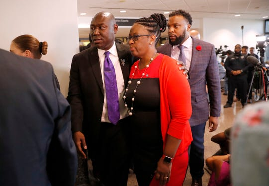 Allison Jean, center, mother of Botham Jean, leaves a news conference with attorneys Ben Crump, left, and Lee Merritt, rear, after the sentencing phase of Dallas police officer Amber Guyger murder trial at Frank Crowley Court Building in Dallas, Wednesday, Oct. 2, 2019. (AP Photo/Tony Gutierrez)