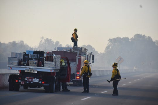 Ventura city firefighters assess flames on either side of Victoria Avenue near Ventura. The blaze erupted early Friday morning.