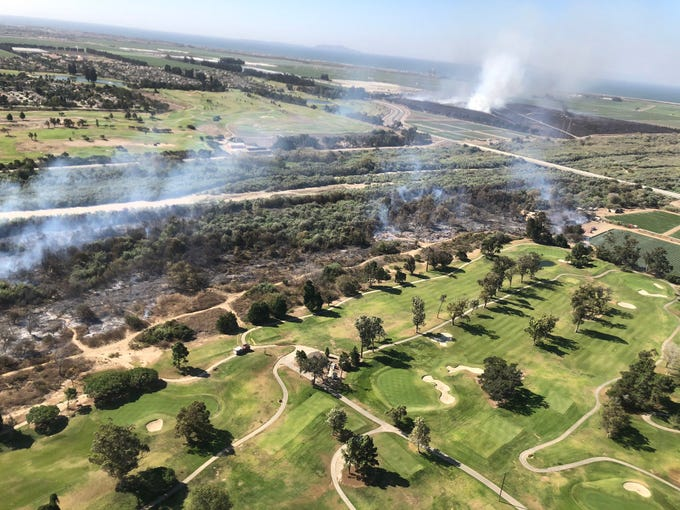 An aerial view of the Olivas Fire in Ventura and Oxnard Friday. The blaze started before dawn near the Santa Clara River and Victoria Avenue and burned in heavy vegetation bordered by golf courses and agricultural land.