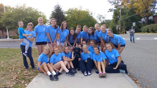 Pleasantville field hockey coach Kristen Coffey (l) joins son, Peyton, members of her team and BluePath service dog Winston (c). The team raised $2,617 this season for BluePath, which trains and supplies service dogs to those with autism. The cause is special to Coffey and her team since Peyton is autistic.