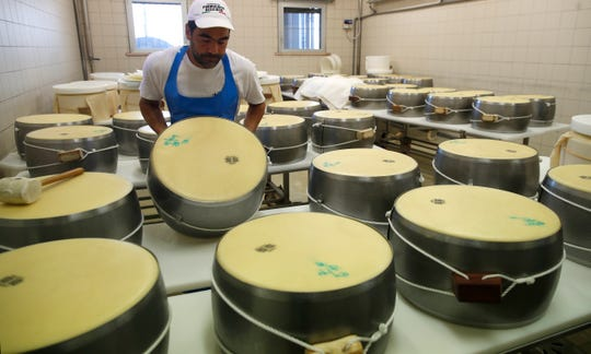 In this photo taken Tuesday, Oct. 8, 2019, Parmigiano Reggiano Parmesan cheese wheels are created in Noceto, near Parma, Italy. U.S. consumers are snapping up Italian Parmesan cheese ahead of an increase in tariffs to take effect next week. The agricultural lobby Coldiretti on Friday, Oct. 11, 2019, said sales of both Parmigiano Reggiano and Grana Padano, aged cheeses defined by their territory of origin, have skyrocketed by 220% since the higher tariffs were announced one week ago.