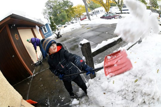 Garrett Simons, 7, helps his grandfather, Dave Salter, shovel snow from the driveway and sidewalks from his home, Friday, Oct. 11, 2019 in Bismarck, N.D. North Dakota Gov. Doug Burgum on Friday activated the state's emergency plan due to what he called a crippling snowstorm that closed major highways and had farmers and ranchers bracing for the potential of huge crop and livestock losses.