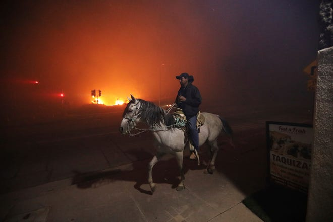 An unidentified man on a horse rides past a wildfire in Sylmar, Calif., Oct. 11, 2019.
