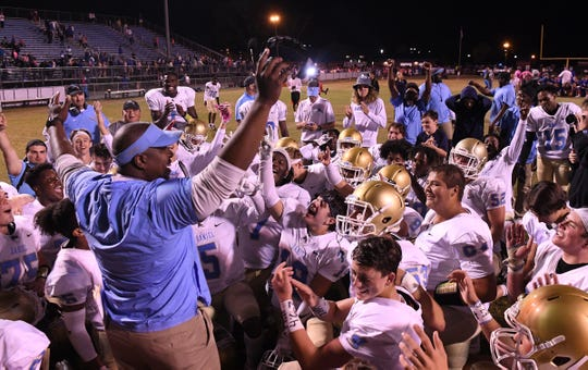 DW Daniel Head Coach Jeff Fruster and the team celebrate a 34-28 win after the game at Wren High School in Piedmont Friday, October 11, 2019.