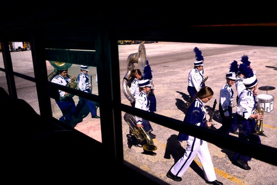 Members of the Roscoe Collegiate High School Marching Band walk past the Hawley High School bus as they make their way to the field for the Big Country Marching Festival.