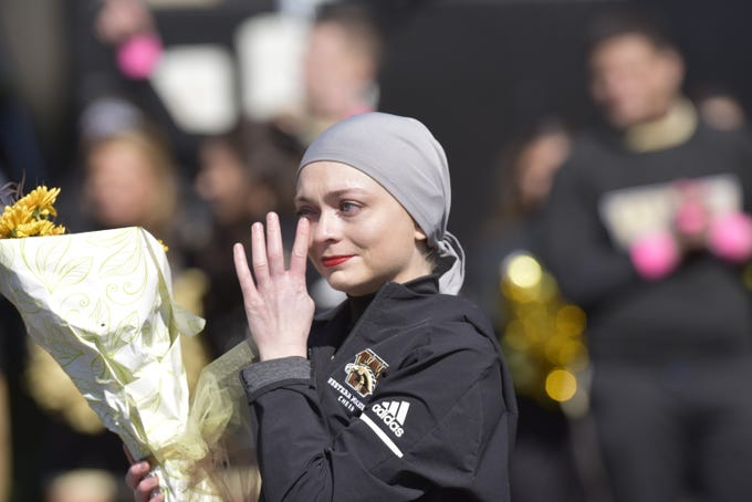 Western Michigan junior cheerleader Brianne Korteway wipes away a tear as it is announced that she is cancer-free after being diagnosed with stage 4 Hodgkins Lymphoma during a ceremony at Waldo Stadium in Kalamazoo on Saturday, Oct. 12, 2019.