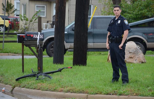 An officer stands near the damaged bicycle which was ridden by a 14-year-old boy who collided with a pick-up on Friday.