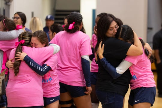 Carroll High School volleyball players embrace before their game against Miller High School on Friday night, following the death of their head coach, Stacy Selby.