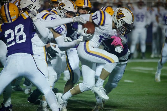 Johnston senior running back Jordan Rusch tries to fight through a narrow opening. Indianola hosted Johnston in a key district game on Oct. 11.