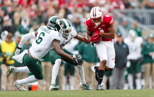 Oct 12, 2019; Madison, WI, USA; Wisconsin Badgers wide receiver A.J. Taylor (4) rushes with the football after catching a pass as Michigan State Spartans cornerback Tre Person (24) and safety David Dowell (6) defend during the second quarter at Camp Randall Stadium.