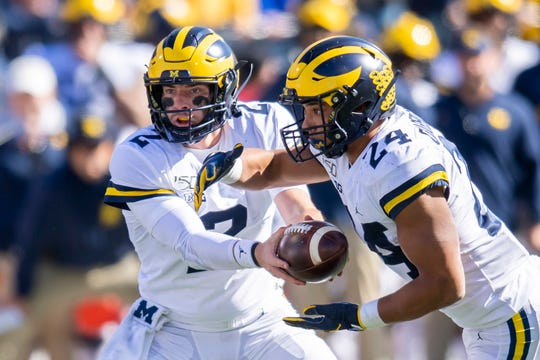 Oct 12, 2019; Champaign, IL, USA; Michigan Wolverines quarterback Shea Patterson (2) hands the ball off to running back Zach Charbonnet (24) during the second half against the Illinois Fighting Illini at Memorial Stadium.