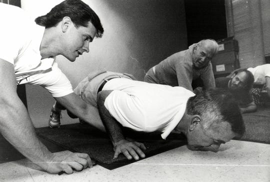 Former Free Press political columnist Hugh McDiarmid does push ups beside the former Freep editor and published Neal Shine for a fitness challenge the Free Press held in 1991.