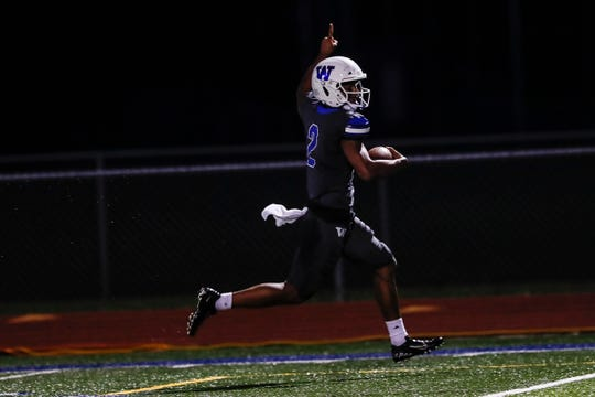 Walled Lake Western wide receiver/defensive back Abdur-Rahmaan Yaseen (2) celebrates as he runs into the end zone against South Lyon during the first half at Walled Lake Western High School in Walled Lake, Friday, Oct. 11, 2019.