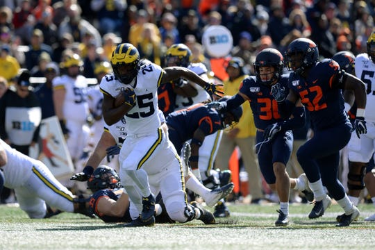 Oct 12, 2019; Champaign, IL, USA; Michigan Wolverines running back Hassan Haskins (25) breaks through the Illinois Fighting Illini defense during the game at Memorial Stadium.