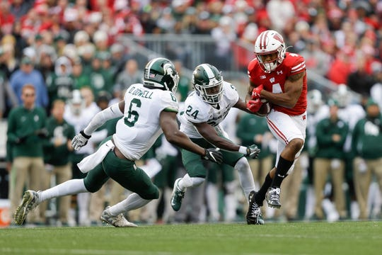 Wisconsin wide receiver A.J. Taylor (4) makes a reception against Michigan State safety David Dowell (6) and cornerback Tre Person (24) during the first half of an NCAA college football game Saturday, Oct. 12, 2019, in Madison, Wis. (AP Photo/Andy Manis)
