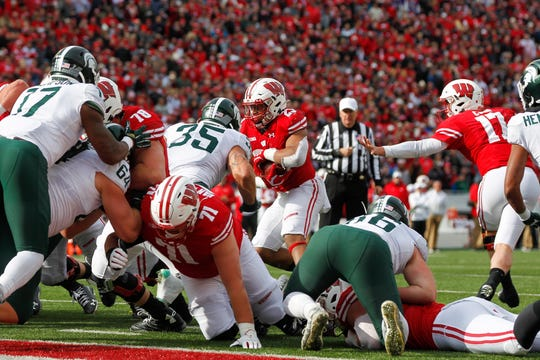 Wisconsin running back Jonathan Taylor (23) runs for a touchdown against Michigan State linebacker Joe Bachie (35) defensive lineman Drew Beesley (86) during the first half of an NCAA college football game Saturday, Oct. 12, 2019, in Madison, Wis. (AP Photo/Andy Manis)