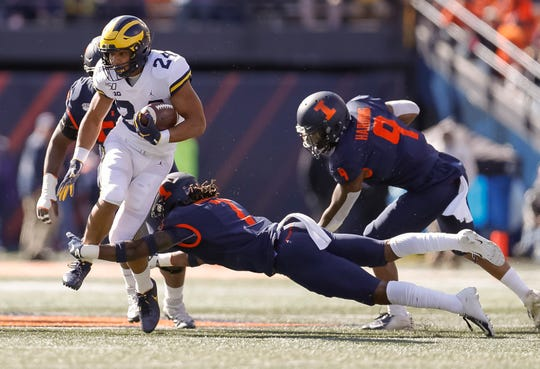 Zach Charbonnet #24 of the Michigan Wolverines runs the ball as Stanley Green #7 of the Illinois Fighting Illini dives for the tackle during the first half at Memorial Stadium on October 12, 2019 in Champaign, Illinois. (Photo by Michael Hickey/Getty Images)