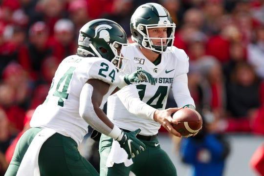 Oct 12, 2019; Madison, WI, USA; Michigan State Spartans quarterback Brian Lewerke (14) hands the football off to running back Elijah Collins (24) during the first quarter against the Wisconsin Badgers at Camp Randall Stadium.