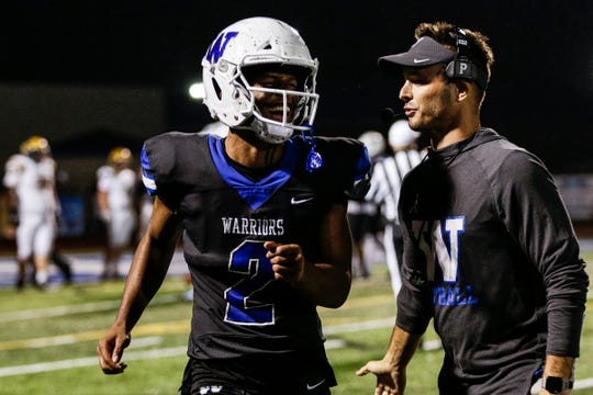 Walled Lake Western receiver/defensive back Abdur-Rahmaan Yassen celebrates a touchdown with head coach Alex Grignon during the second half against South Lyon in Walled Lake, Friday, Oct. 11, 2019.
