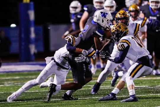 Walled Lake Western wide receiver/defensive back Abdur-Rahmaan Yaseen (2) is stopped by South Lyon defensive back Quinn Fracassi (10) and Jake Newman (25) during the first half at Walled Lake Western High School in Walled Lake, Friday, Oct. 11, 2019.