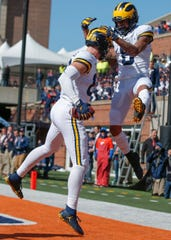 Luke Schoonmaker #86 of the Michigan Wolverines and Ronnie Bell #8 of the Michigan Wolverines celebrate a touchdown during the first half against the Illinois Fighting Illini at Memorial Stadium on October 12, 2019 in Champaign, Illinois. (Photo by Michael Hickey/Getty Images)