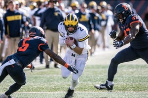 Michigan's Shea Patterson runs the ball as Illinois' Tony Adams (6) and Oluwole Betiku Jr. (47) close in during the second half.