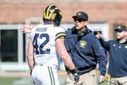 Michigan coach Jim Harbaugh talks with Ben Mason during the first half.