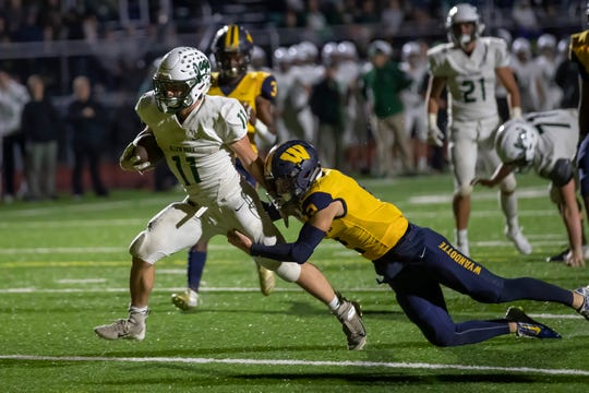 Allen Park's Nico Tiberia (11) breaks a tackle from Wyandotte Roosevelt's Hayden Loya and scores his second first-half touchdown on Friday.