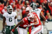 Wisconsin wide receiver Quintez Cephus (87) celebrates a touchdown with teammate Jake Ferguson (84) as Michigan State safety David Dowell (6) and Xavier Henderson react during the first half.