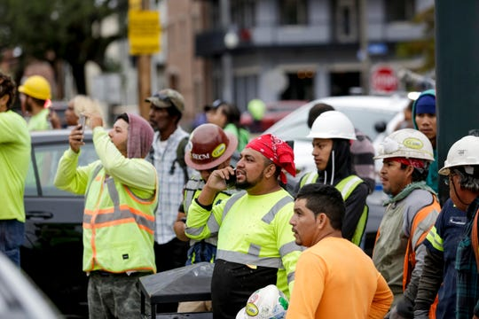 Construction workers look on after a large portion of a hotel under construction suddenly collapsed in New Orleans on Saturday, Oct. 12, 2019.