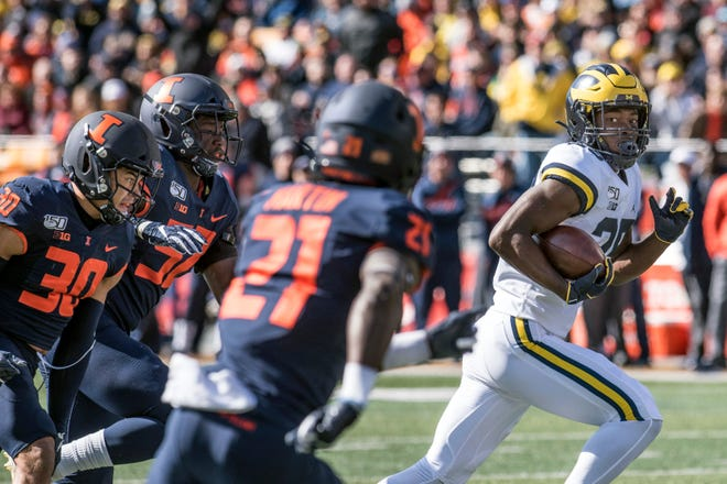Michigan's Hassan Haskins runs away from the Illinois defense to score a touchdown last week.