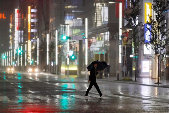 A man walks a pedestrian crossing at Ginza shopping district in the pouring rain due to Typhoon Hagibis in Tokyo Saturday, Oct. 12, 2019.