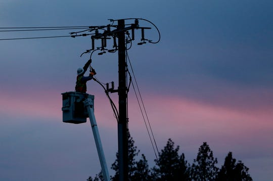FILE - In this Nov. 26, 2018, file photo, a Pacific Gas & Electric lineman works to repair a power line in fire-ravaged Paradise, Calif. PG & E anticipates shutting off power in 9 California counties due to hot, dry and windy conditions even as it formalizes settlements with the vast majority of claims from the deadly Northern California wildfires in 2017 and 2018.