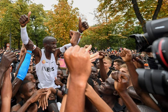 Eliud Kipchoge celebrates after breaking the historic two-hour barrier for a marathon in Vienna Saturday.