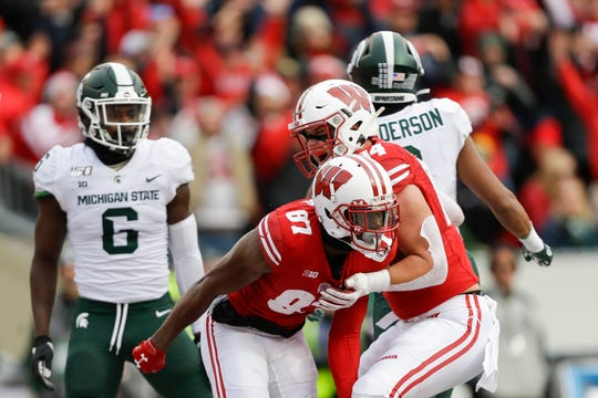 Wisconsin wide receiver Quintez Cephus (87) celebrates a touchdown with teammate Jake Ferguson (84) as Michigan State safety David Dowell (6) and Xavier Henderson (3) look on.