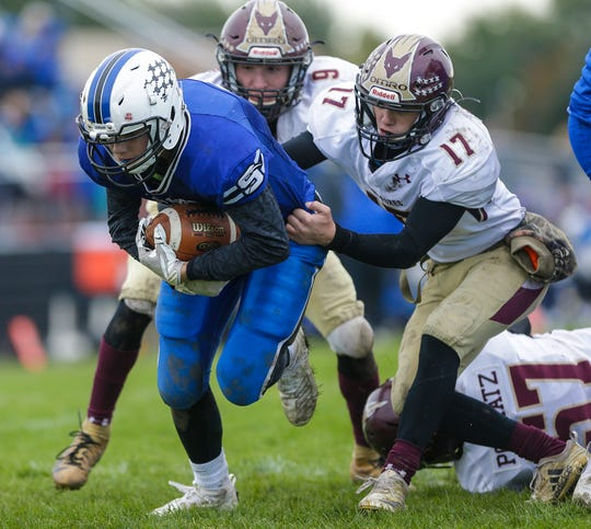St Mary's Springs' Isaac Hyland runs in for a touchdown while being defended by Omro's Cooper Krockstrom (9) and Ben Wellhoefer (17) during Saturday's game in North Fond du Lac.
