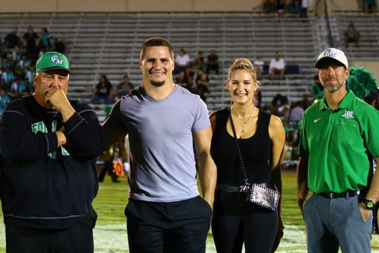 Fort Myers coach Sam Sirianni Jr. stands with North Fort Myers grad and NFL free agent fullback Tommy Bohanon, his wife Katie and Fort Myers athletic director Steve Cato in a halftime ceremony where Bohanon represented the NFL and gave Sirianni two tickets to Super Bowl LIV.