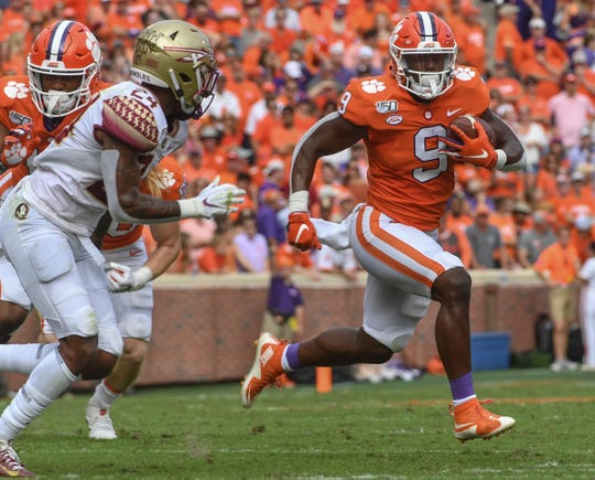 Clemson running back Travis Etienne (9) runs by Florida State defensive back Cyrus Fagan(24) during the first quarter at Memorial Stadium before the game with Florida State in Clemson, South Carolina Saturday, October 12, 2019.