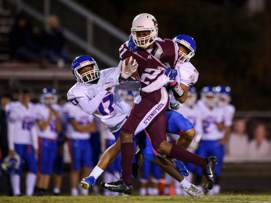 Henderson's Myekel Sanners (21) is brought down by two Apollo Eagles defenders during the third quarter at Colonels Stadium in Henderson, Ky., Friday, Oct. 11, 2019. The Colonels defeated the Eagles, 20-13.