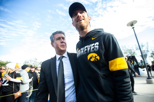 Iowa quarterbacks coach Ken O'Keefe, left, and former quarterback Ricky Stanzi chat while players arrive before a NCAA Big Ten Conference football game between the Iowa Hawkeyes and Penn State, Saturday, Oct., 12, 2019, at Kinnick Stadium in Iowa City, Iowa.