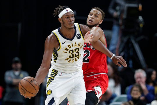 Chicago Bulls forward Daniel Gafford (12) reaches for the ball around Indiana Pacers center Myles Turner (33) during the second half of an NBA preseason basketball game in Indianapolis, Friday, Oct. 11, 2019. (AP Photo/Michael Conroy)