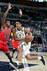Indiana Pacers guard Malcolm Brogdon (7) drives on Chicago Bulls guard Kris Dunn (32) during the first half of an NBA preseason basketball game in Indianapolis, Friday, Oct. 11, 2019. (AP Photo/Michael Conroy)