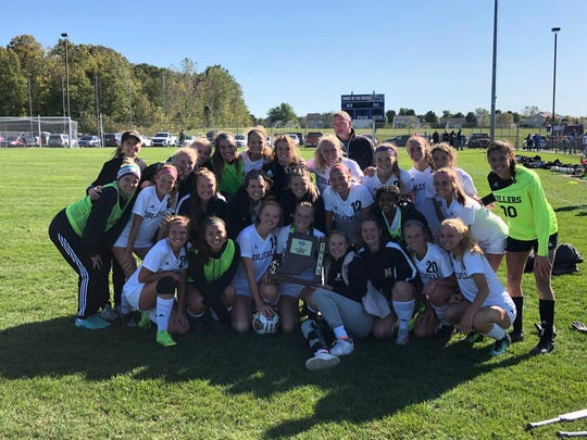 Noblesville girls soccer players pose with their sectional trophy after beating Hamilton Southeastern on Saturday afternoon.