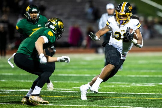 Bettendorf's Harrison Bey-Buie (32) reaches out to stiff arm a Cedar Rapids Kennedy defender during a Class 4A varsity football game, Friday, Oct., 11, 2019, at Kingston Stadium in Cedar Rapids, Iowa.